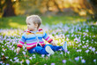 Baby girl in knitted clothes sitting on the grass with blue hyacinths