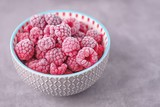 Frozen raspberries in a gray bowl on a gray beton background