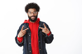Waist-up shot of satisfied and friendly smiling african american bearded man with afro hairstyle in glasses, denim jacket over red hoodie grinning at camera and showing victory sign over gray wall