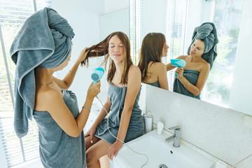 Mom brushing hair to her daughter in hotel bathroom © Alena Ozerova