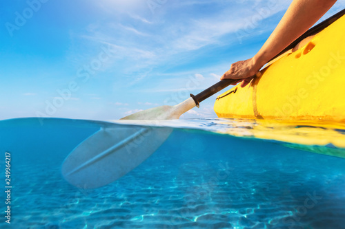 Leinwandbild Motiv Split view of person kayaking in transparent blue sea, underwater and above water photography of kayak and paddle in warm summer tropical travel destination for vacation holidays