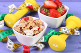 Strawberries, wheat and rye flakes, dumbbells and centimeter, healthy and sporty lifestyle