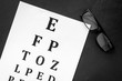 Eye examination. Eyesight test chart and glasses on black background top view - 249974872
