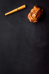 Buddhist symbol. Oriental wooden frog on black background top view space for text © 9dreamstudio