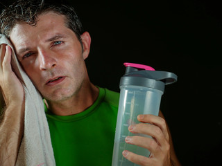 sweaty tired and exhausted sport man with water bottle cooling off after hard fitness workout at gym club isolated on black background in healthy lifestyle and training sacrifice © TheVisualsYouNeed