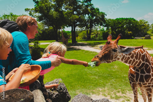 Leinwanddruck Bild father and kids feeding giraffes in zoo