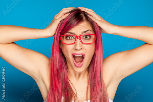 Leinwanddruck Bild Shocked woman with a pink hair and glasses on blue background
