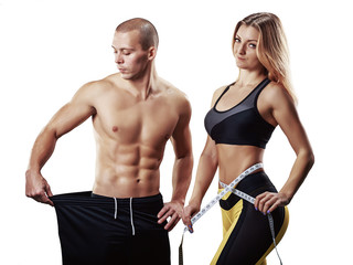 Athletic couple isolated over white background. Muscular Man and Woman with measuring tape in gym. Weight loss, bodybuilding, sport and fitness, coach, workout, dieting and health. - Image © kuznetsov_konsta