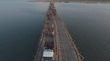 aerial drone shot : low fly over traffic jam on the bamboo bridge over the Mekong River at the end of the day