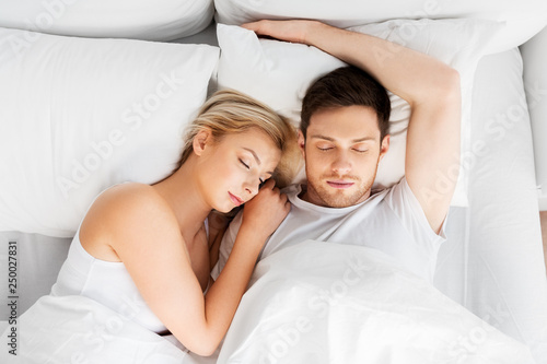 Leinwanddruck Bild people, rest and relationships concept - happy couple sleeping in bed at home