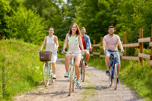people, leisure and lifestyle concept - happy young friends riding fixed gear bicycles on country road in summer
