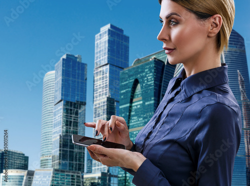 Business woman with smartphone stands over cityscape background.