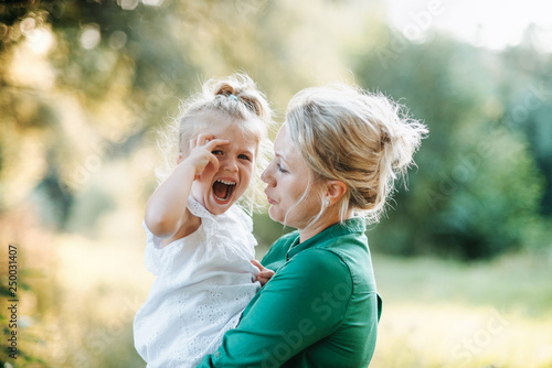 mata magnetyczna Young mother comforting crying small daughter in summer in nature.