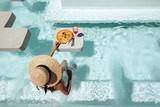 Girl eating pizza in pool - 250034200