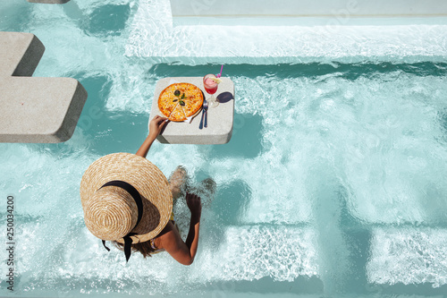 Leinwanddruck Bild Girl eating pizza in pool