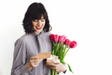 Fototapeta Tulipany - Beautiful brunette girl holding bouquet of tulips, gift box and greeting card on white background indoors, space for text. Happy young woman with flowers. Happy mothers day. © sonyachny