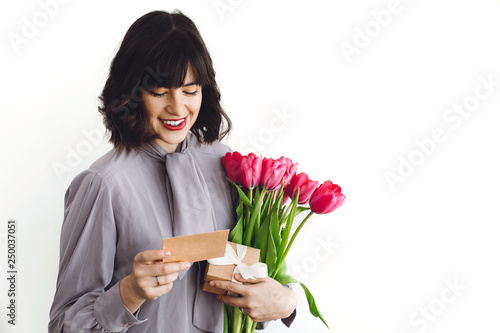Beautiful brunette girl holding bouquet of tulips, gift box and greeting card on white background indoors, space for text. Happy young woman with flowers. Happy mothers day. - 250037051