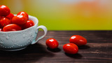 close up view of cherry tomatoes on wooden board with blurred background