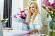 selective focus of beautiful female florist arranging and wrapping bouquet in flower shop