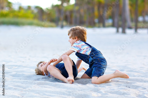 Leinwandbild Motiv Two little kids boys having fun on tropical beach, happy best friends playing, friendship concept. Siblings brothers, twins fighting, running and jumping in family look with palms trees on background.