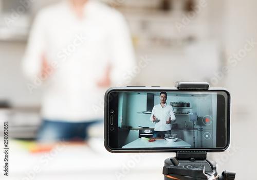 Man on the kitchen filming video. Vlogging concept. © dmitrimaruta