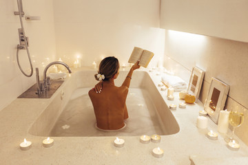 Woman relaxing in bath with candles © Alena Ozerova