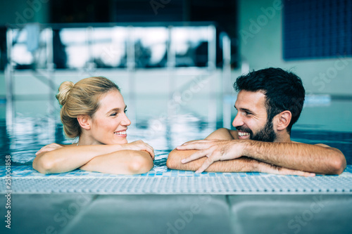 canvas print picture Happy attractive couple relaxing in swimming pool