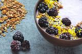 Colorful healthy breakfast bowl with pink yogurt and blackberries.