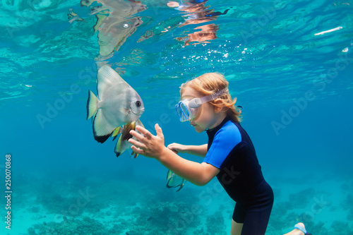 Leinwanddruck Bild Happy family - active kid in snorkeling mask dive underwater, see tropical fish Platax ( Batfish ) in coral reef sea pool. Travel adventure, swimming activity on summer beach vacation with child.