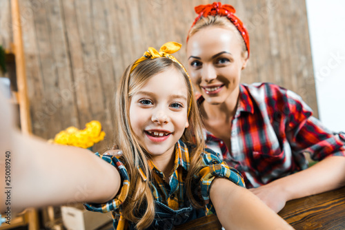 Leinwanddruck Bild selective focus of cheerful kid taking selfie with beautiful mother