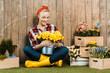 Leinwandbild Motiv happy woman sitting with crossed legs and looking at flowers in bucket