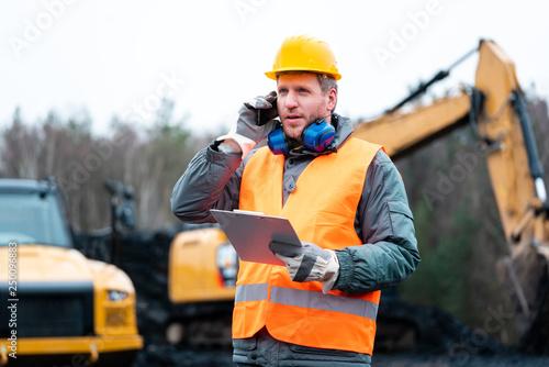 Leinwandbild Motiv Porträt eines Arbeiters im Tagebau vor einem Bagger
