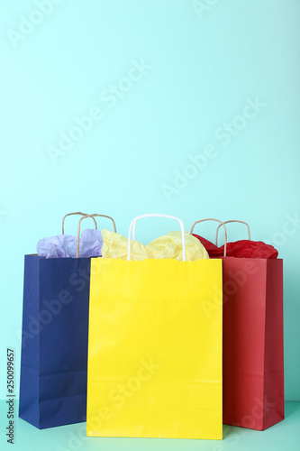 Colorful paper shopping bags on mint background
