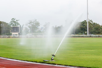 System working on fresh green grass on football or soccer stadium. Sprinkler watering field football. Automatic water irrigation in action. Close-up sprinkler of automatic watering.  © kanpisut
