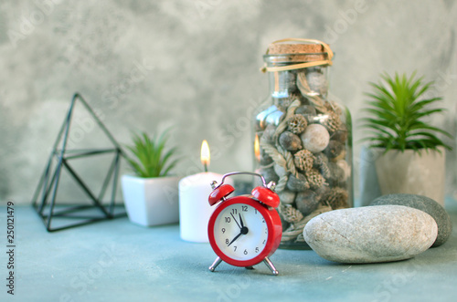 Still life details. Nordic mood in office interior with clock, plants, candle and other decor on a desktop. Scandinavian style in the interior concept. © Dmytro