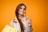 Portrait of happy nice girl with curly hair holding bags and credit card after shopping isolated over the yellow background - 250134489
