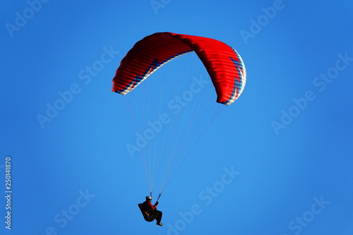 Red paraglider in a blue sky © NUI BLANCO