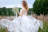 Portrait of attractive young stylish bride in white wedding dress with wedding bouquet in the hand, make up and hairstyle