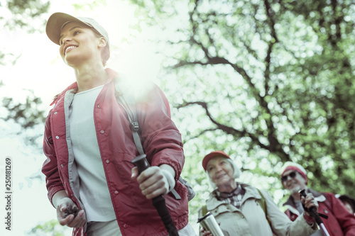 Young hiking guide feeling inspired by elderly tourists