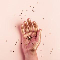 Female golden hand with golden stars closeup. Art Creativity Concept © colnihko