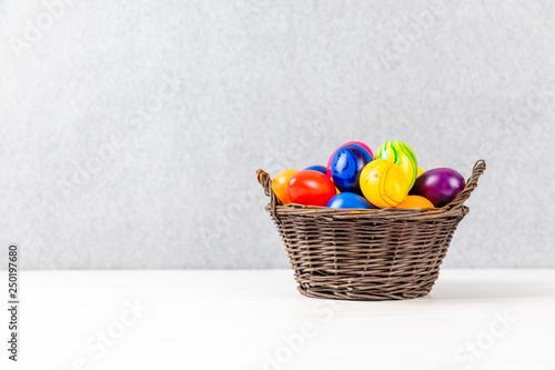 Leinwandbild Motiv colorful easter eggs in a basket with gray background
