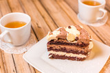 Cake delicious on plate. Bakery, cream dessert cake with tea spot on wooden table