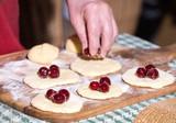 Woman making dumplings with cherries