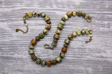 A malachite beads and a bracelet on a gray wooden background