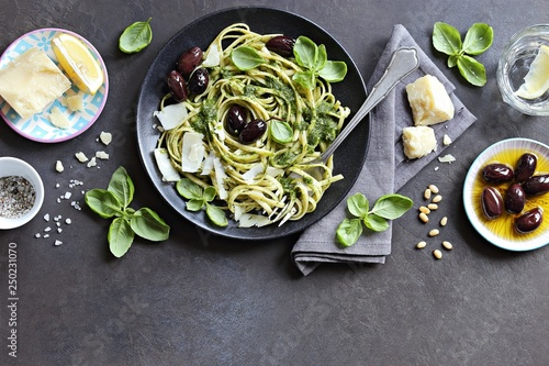 Spaghetti with basil pesto, black olives and parmesan cheese. Traditional Italian pasta in black plate on dark background . Overhead view, copy space - 250231070
