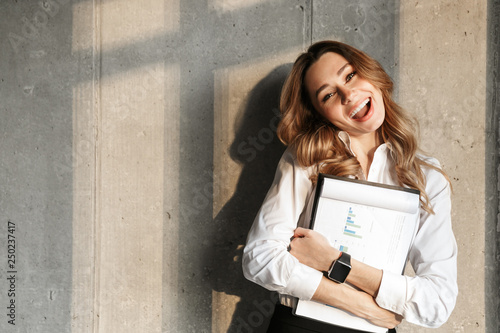 Beautiful young business woman dressed in formal clothes shirt indoors holding documents.