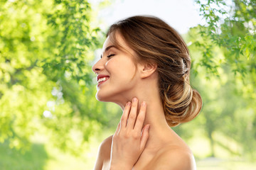 beauty and people concept - smiling young woman touching her neck over green natural background © Syda Productions