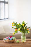 easter, holidays, tradition and object concept - colored eggs in basket and tulip flowers at home