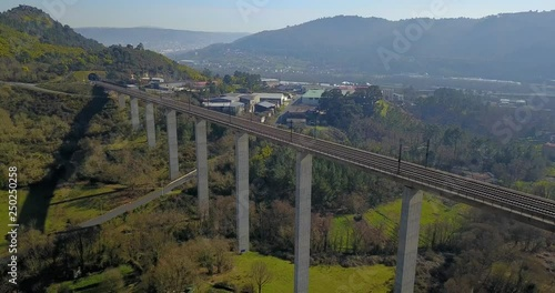 TRAIN BRIDGE IN A GREEN VALLEY WITH FACTORIES, HOUSES AND THE CITY OF OURENSE