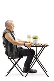 Old punk man sitting at a table and drinking beer - 250259088